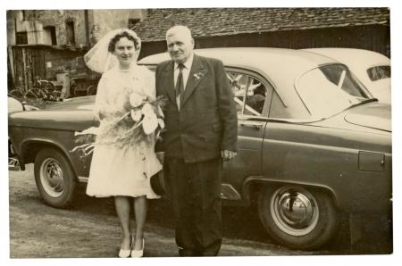 PRAGUE, CZECHOSLOVAKIA, CIRCA 1955 - Bride and her father posing with a car in a farmyard - circa 1955 Stock Photo