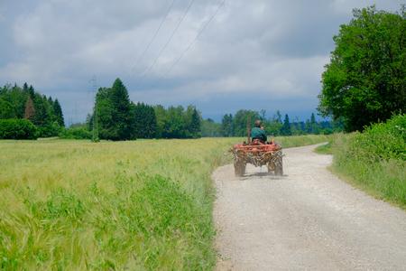 rusty car: Tractor Driving on Rural Road, Gorenjska, Slovenia. Stock Photo