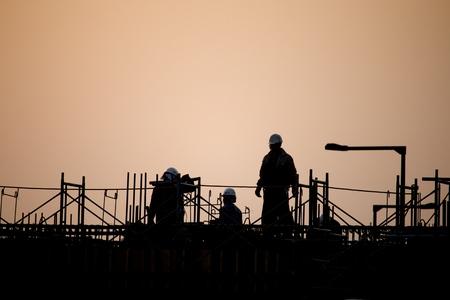 夕日の建設現場で働く人たち