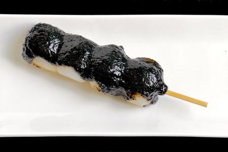 Skewered dumplings. Skewered ball shaped rice cakes. Sweet sauce of black sesame seeds.