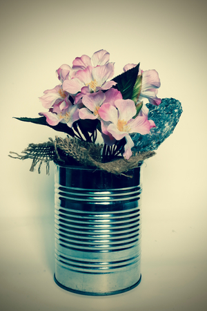 contoured: Empty cans and cherry blossoms of artificial flowers