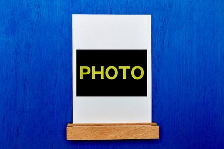 青い壁に立つピクチャースタンド 写真素材