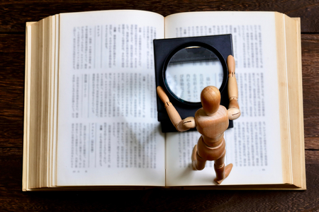 A wooden figurine on an open book, reading concept