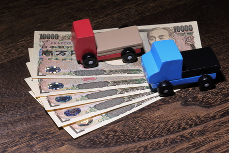 円通貨と車のおもちゃ木のテーブル
