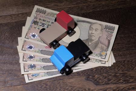 木製テーブルの上の円通貨と車のおもちゃ