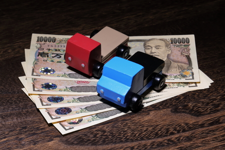 Yen currency and car toys on wooden table 写真素材