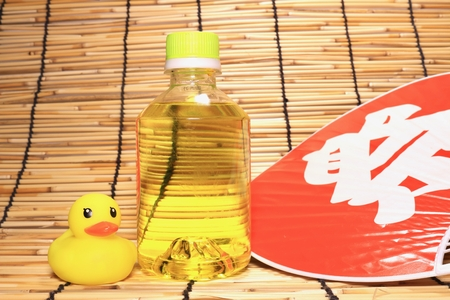 A bottled drink, a hand fan and a yellow rubber duck on a blind Stock fotó