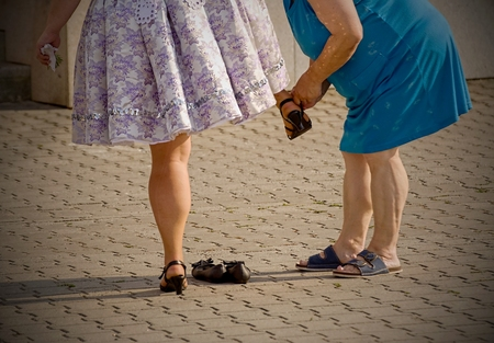 fastens: Mother on slippered  fastens the shoe of his daughter. Stock Photo
