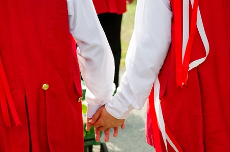 feast: Young lovers in folk costume holding hands on moravian feast.