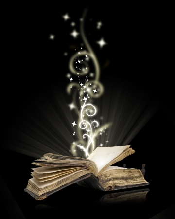 Opened book magic on black  photo
