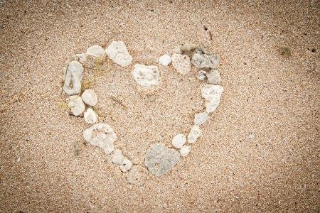 Shells on the ocean beach, heart shape background photo