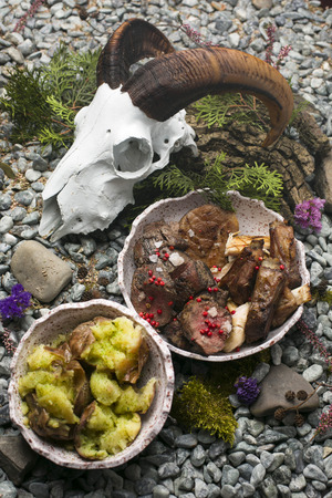 donner: Tasty juicy grilled meat with boiled steamy hot potatoes on a rocks with skull.