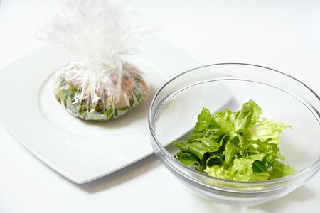 white sleeve: Vegetable wrapped in a special baking sleeve and salad isolated on white Stock Photo