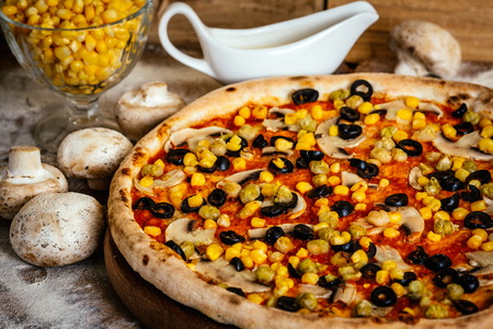 Pizza with corn, olives and mushrooms on wood background with ingredients