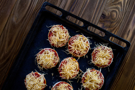 semifinished: Small semifinished pizzas with mozzarella cheese, lettuce and cherry tomatoes on the baking pan on a wooden background Stock Photo