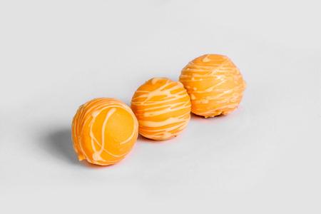 Orange chocolate truffles on white background