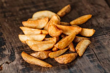 Baked potato wedges on wood background