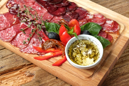 Cutting board with assorted smoked meat on wooden background 写真素材