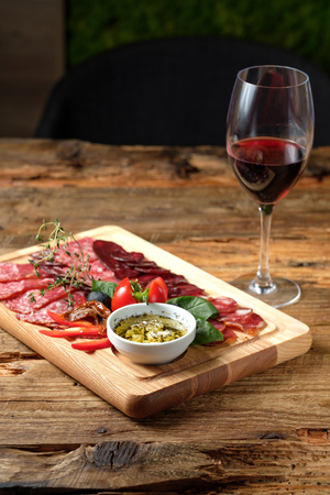 Glass of red wine and cutting board with assorted smoked meat on wooden background