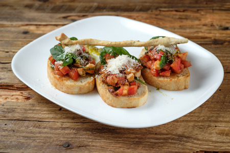 Bruschetta with fresh tomatoes, parmesan and basil on a wooden background