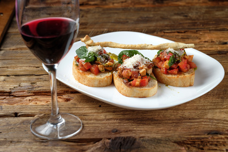 Glass of red wine and bruschetta with fresh tomatoes, parmesan and basil on a wooden background