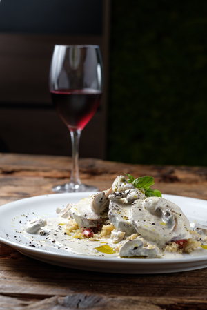 Baked veal with mushroom and sauce served with couscous. Glass of red wine on wood background