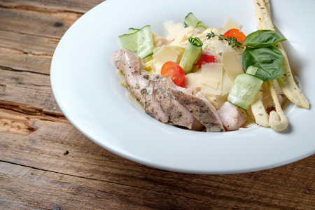 Sliced tuna with pasta, parmezan, vegetables and basil on wood background