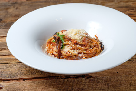 Pasta with tomato sauce, sun dried tomatoes, parmesan and basil on wood background 写真素材