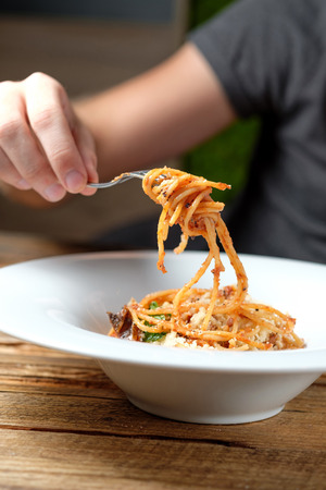 Mans hand holding a fork with spaghetti over a plate. Pasta with tomato sauce, sun dried tomatoes, parmesan and basil on wood background