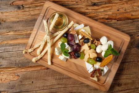 Cheese platter with assorted cheeses, grapes, olives, grissini and honey on the cutting bord wood background. Italian cheese and fruit platter. Top view Stock Photo