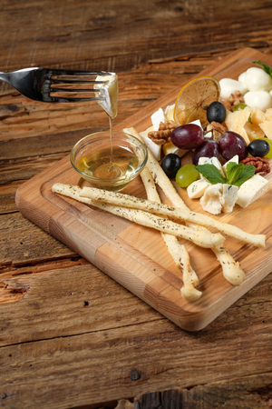 Piece of cheese on fork above the cheese platter on wood background 写真素材
