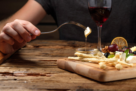 Mans hand holding a fork with a piece of cheese above the cheese platter on wood background 写真素材