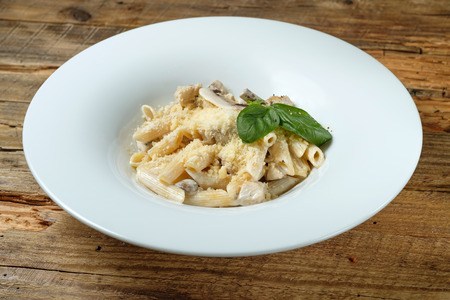 Pasta with cheese, chicken and mushroom on wood background 写真素材