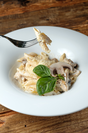 Fork with pasta. Pasta with cheese, chicken and mushroom on wood background 写真素材