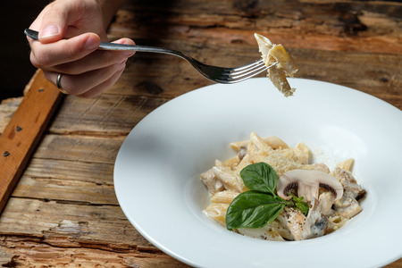 Mans hand holding a fork with pasta. Pasta with cheese, chicken and mushroom on wood background 写真素材