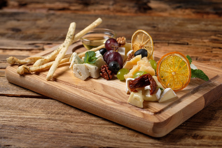 Cheese platter with assorted cheeses, grapes, olives, grissini and honey on the cutting bord wood background. Italian cheese and fruit platter