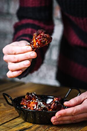 female hands holding fried chicken wing over the plate