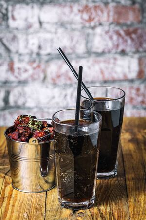 Two glasses of soft drink and bucket of chicken fryed wings on wood table