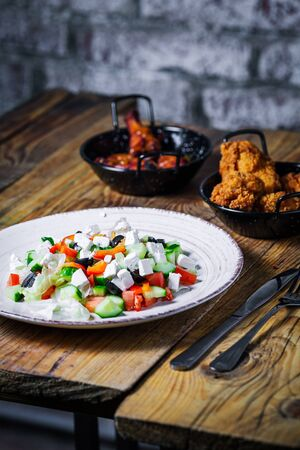 Greek salad and chicken snack plates on wood table 写真素材