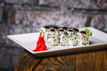 Plate of vegeterian sushi and chopsticks on wood background