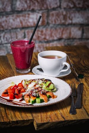 Plate of salmon salad, glass of berry smoothies and cup of tea on wood bakground