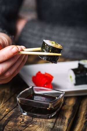 Hands hold sushi with chopsticks
