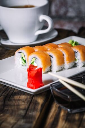 Sushi rolls and cup of tea on wood background. Sushi menu. Japanese food