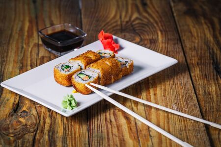 Plate of fried roll on wood background