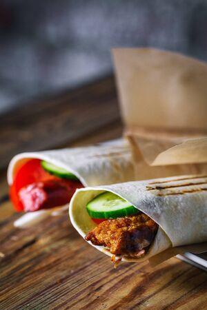 Shawarma sandwich - fresh roll of thin lavash (pita bread) on a wooden background