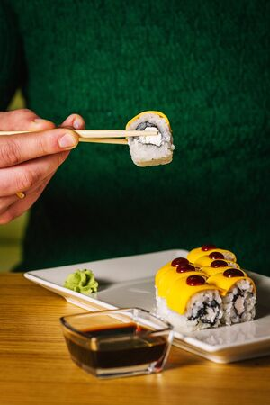 Mens hands hold sushi with chopsticks over table 写真素材