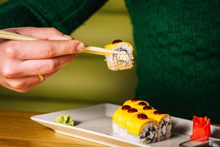 Mens hands hold sushi with chopsticks over plate