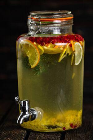Homemade lemonade in beverage dispenser with fresh fruits on wood background 写真素材