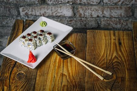 Plate of sushi on wooden table in front of stone wall