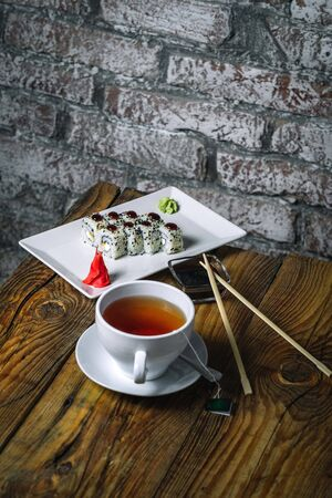 Sushi rolls and cup of tea on wood background. Sushi menu. Japanese food.